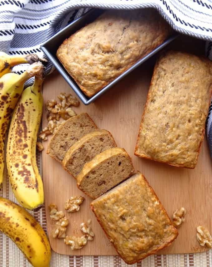vegan banana bread in a loaf pan with another loaf cut in pieces and ripe bananas and walnuts on the side
