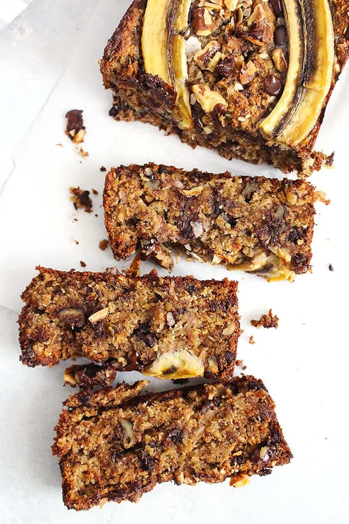 three pieces of a vegan banana bread on a white surface with a loaf of banana bread in the background