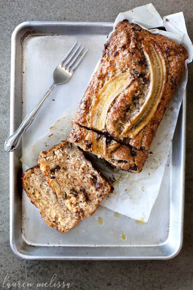a vegan banana bread on a tray with baking paper and a fork on the side
