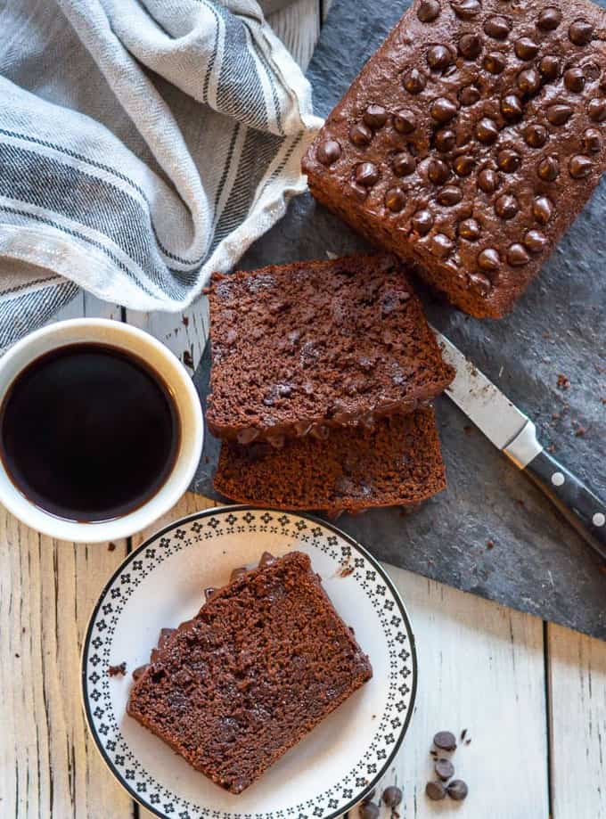 a chocolate banana bread on a white board with a cup of coffee and a slice of banana bread on a small plate