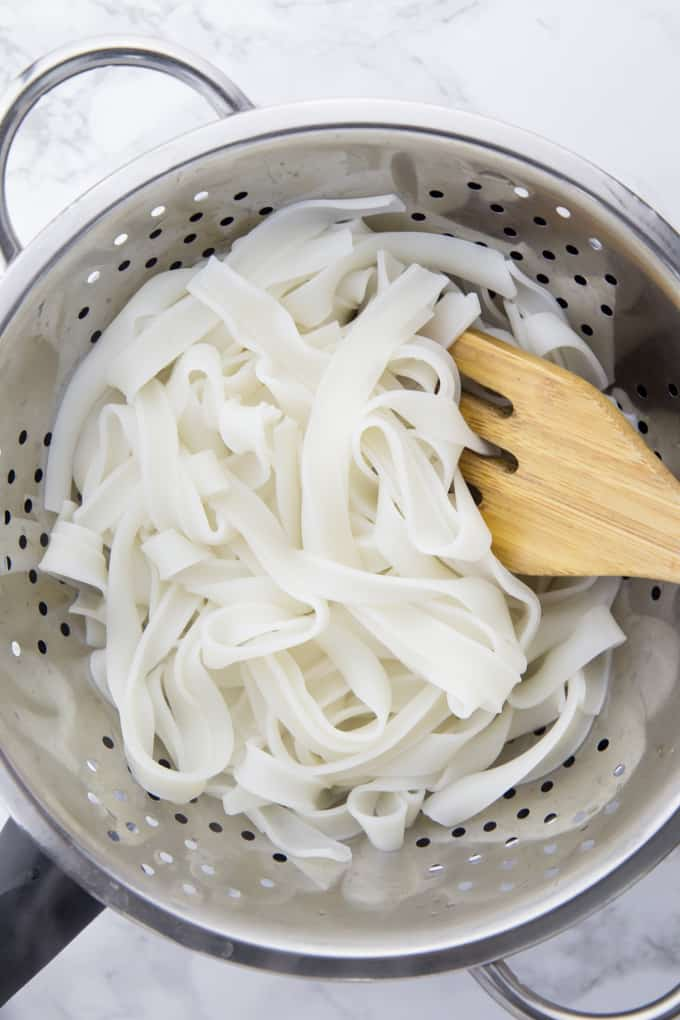 cooked rice noodles in a colander with a wooden spoon