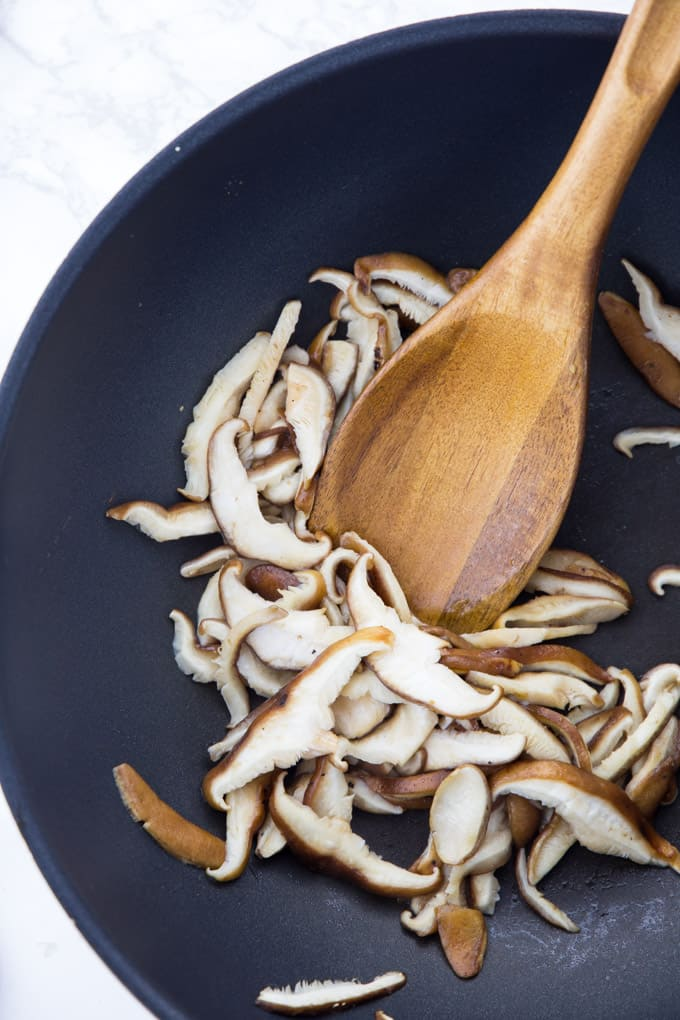 The sliced shiitake mushrooms are being cooked in a pan with a wooden spoon