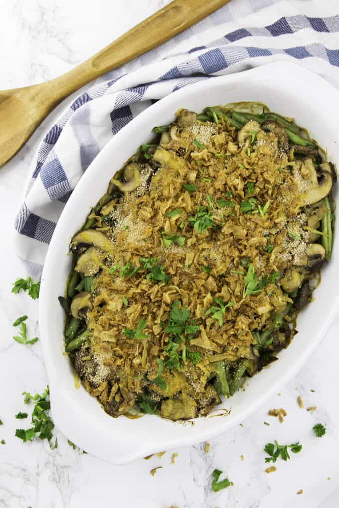 vegan green bean casserole is a casserole dish on a marble counter top with a wooden spoon and a blue and white table cloth on the side