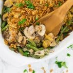 close-up photo of a vegan green bean casserole in a white casserole dish with a wooden spoon and chopped parsley and fried onions on top