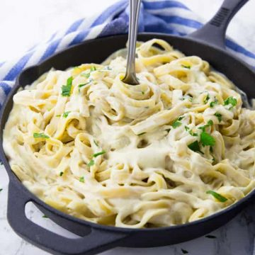 fettuccine with vegan cauliflower Alfredo sauce in a black pan with a fork and a blue dish cloth in the background