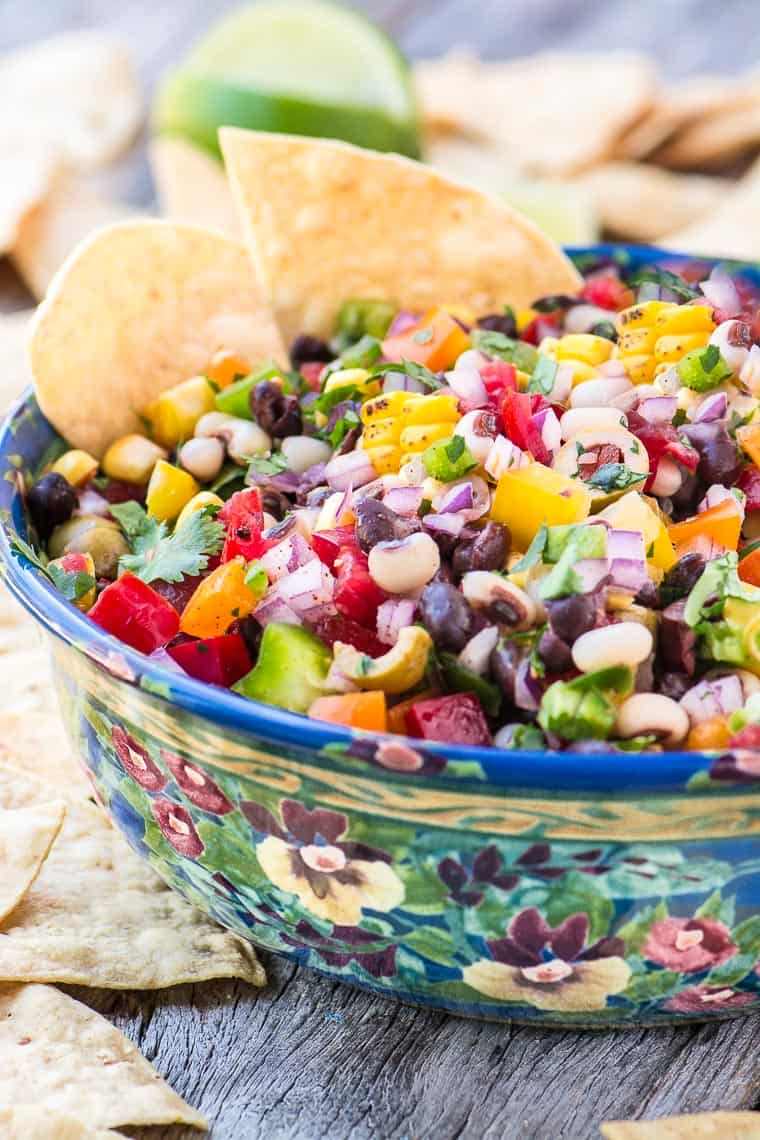 a bowl of cowboy caviar on a wooden counter top with nachos on the side and lime halves in the background