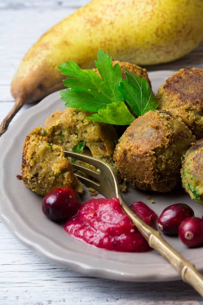 festive vegan falafel with cranberry pear sauce on a grey plate with a pear in the background