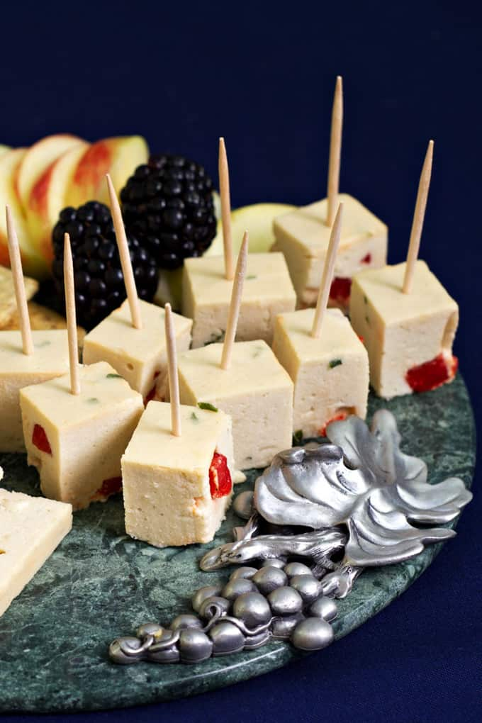 vegan cheeze cubes with toothpicks on a metal plate with a black background