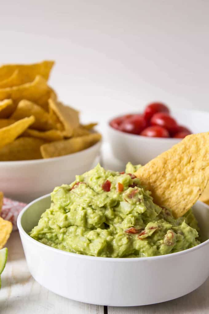 a bowl of guacamole on a white counter tip with another bowl of nachos and cherry tomatoes in the background