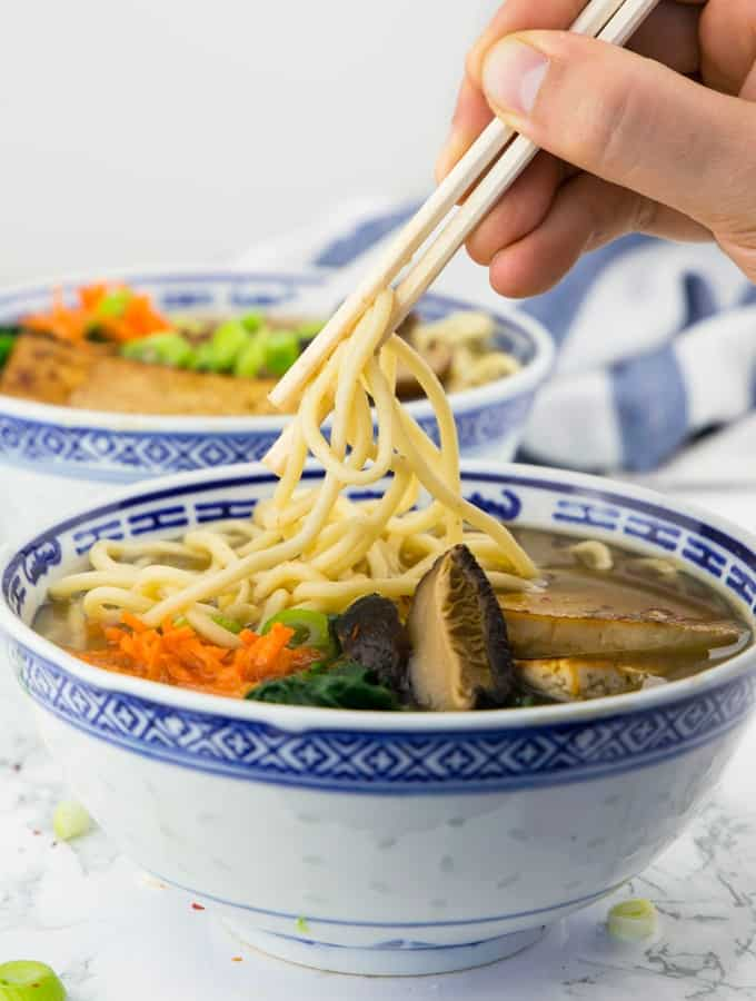 a hand picking up some noodles out of a bowl of vegan ramen with chop sticks with another bowl of vegan ramen in the background