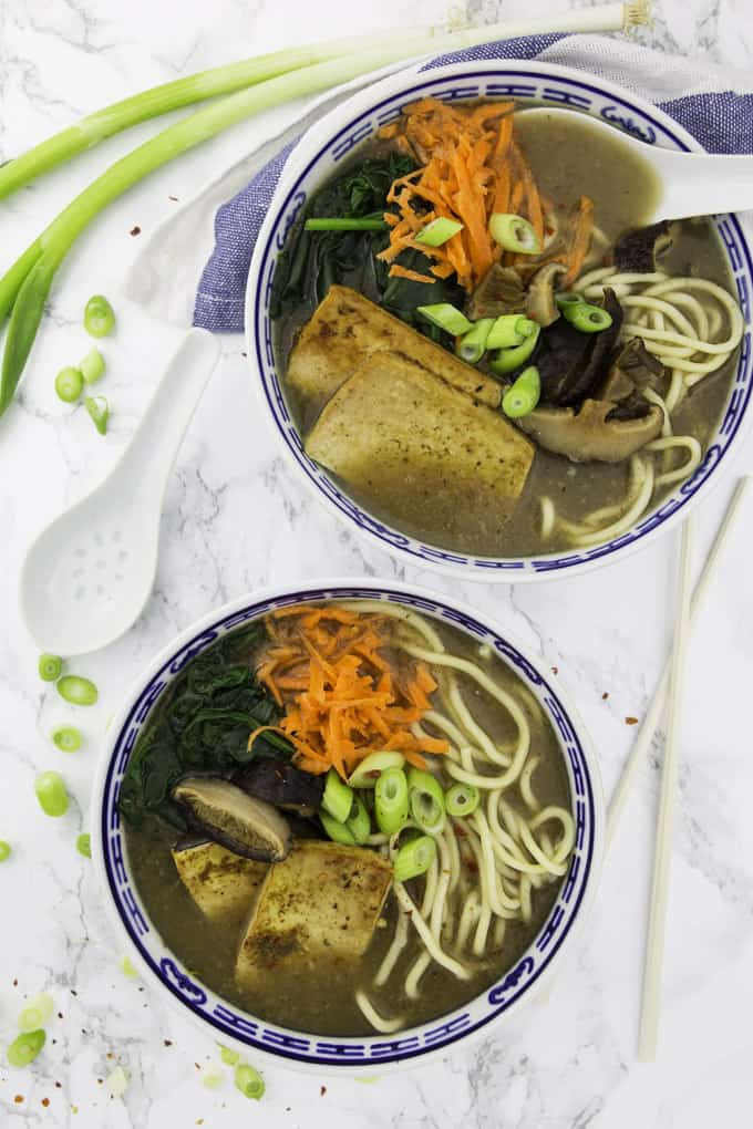 two bowls of vegan ramen on a marble counter top with chop sticks, a spoon, and green onions on the side