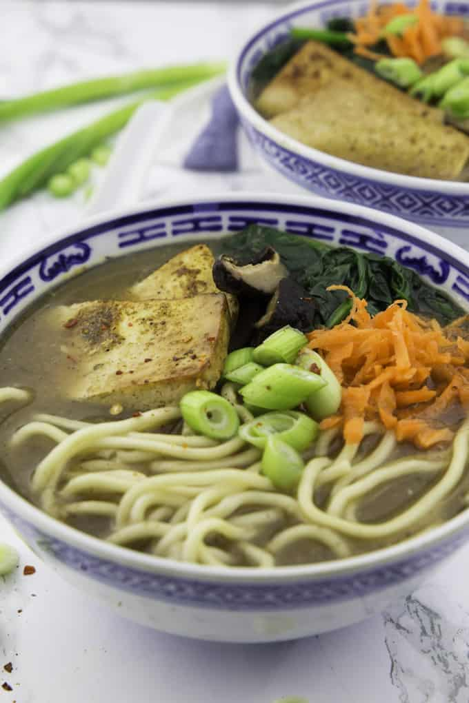 a bowl of vegan ramen with green onions on top on a marble counter top with another bowl in the background