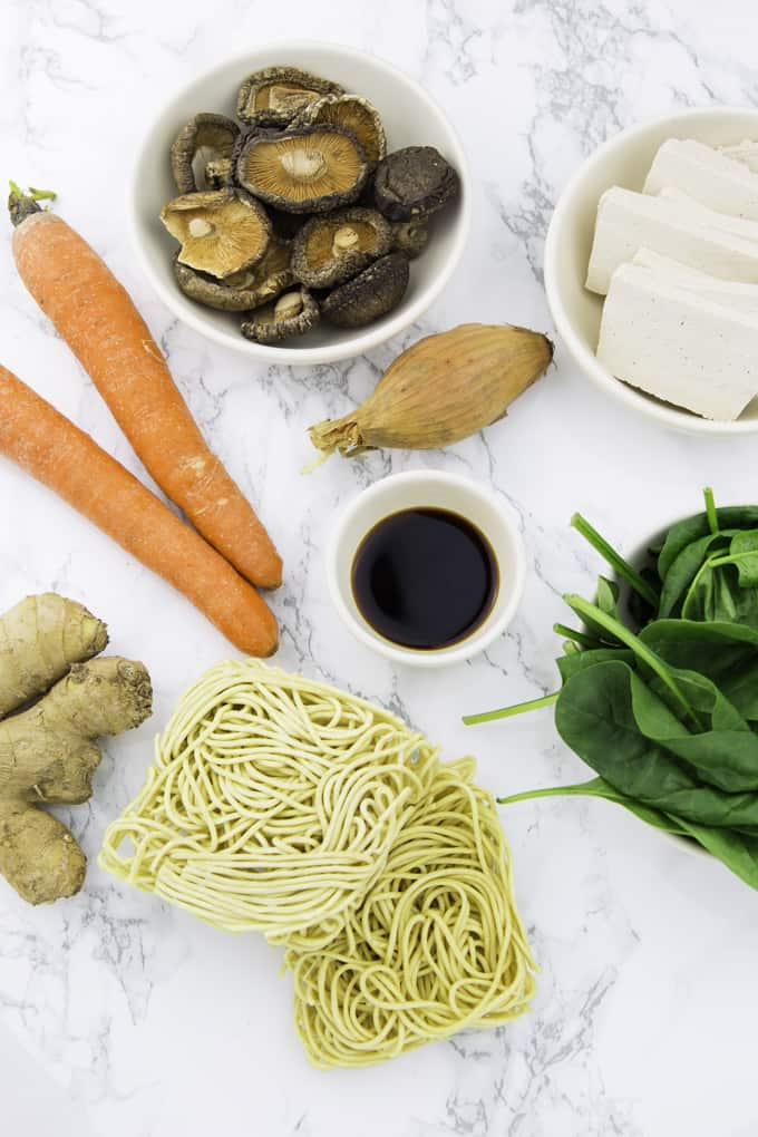 ingredients for vegan ramen on a marble counter top (carrots, dried shiitake, ginger, fresh spinach, tofu, and ramen noodles)