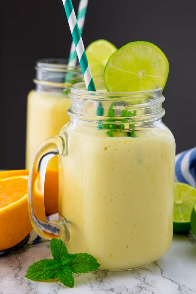 a glass of mango smoothie with lime wedges, mint leaves, and a blue straw on a marble counter top with another glass in the background