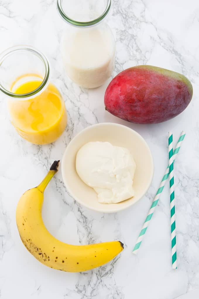 a banana, a mango, two glass bottles with almond milk and orange juice, and a small bowl with yogurt on a marble counter top (ingredients for a mango smoothie)
