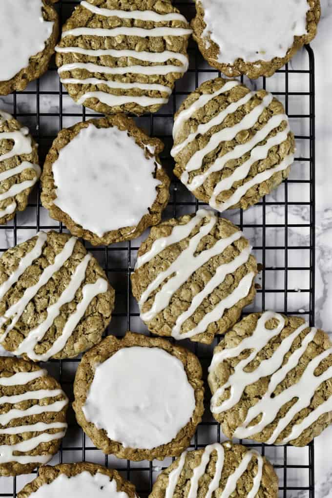 vegan oatmeal cookies with icing on a cooling rack