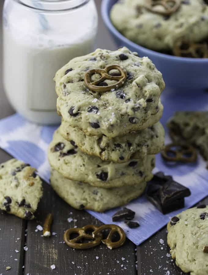 a stack of Chocolate Chip Pretzel Cookies with a glass of plant-based milk in the background