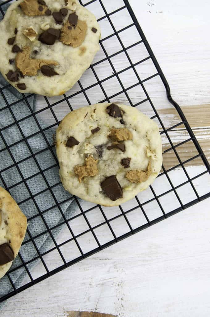 two chunky monkey cookies on a cooling rack on a white wooden board with a blue dish cloth