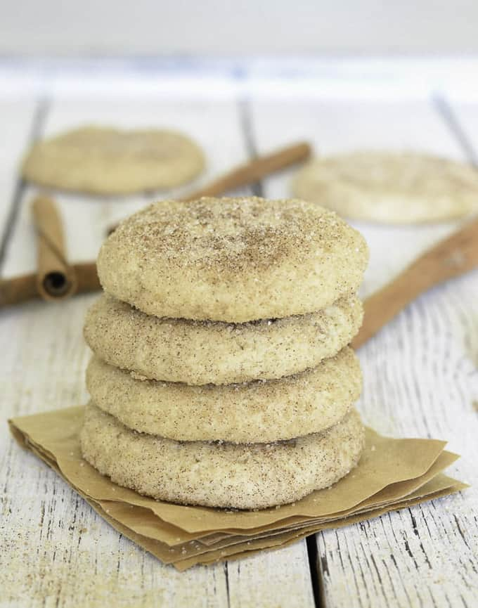 a stack of four vegan snickerdoodle cookies on a white board with more snickerdoodles in the background