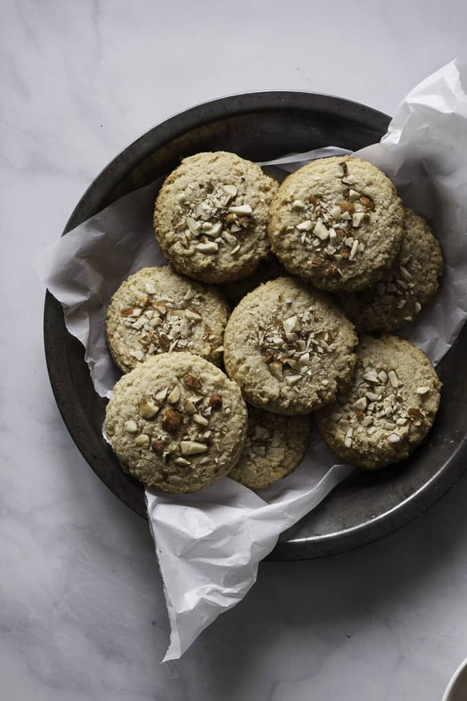Gluten-Free Maple Almond Cookies in a dark bowl with parchment paper on marble counter top