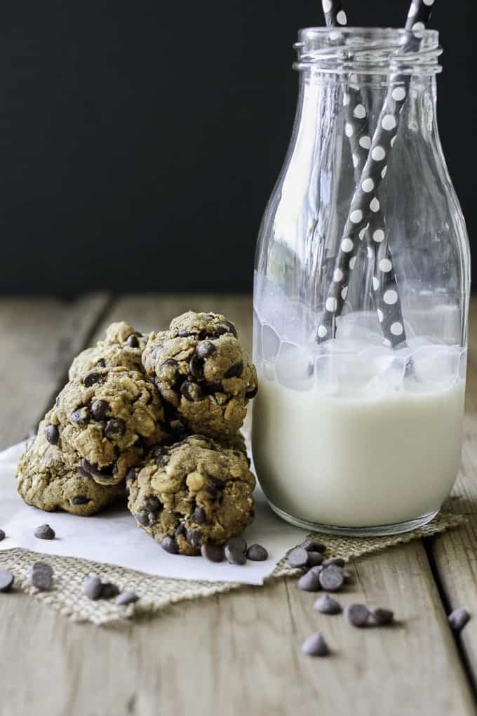 a stack of Oatmeal Chocolate Chip Cookies with a bottle of plant-based milk with two straws on the side