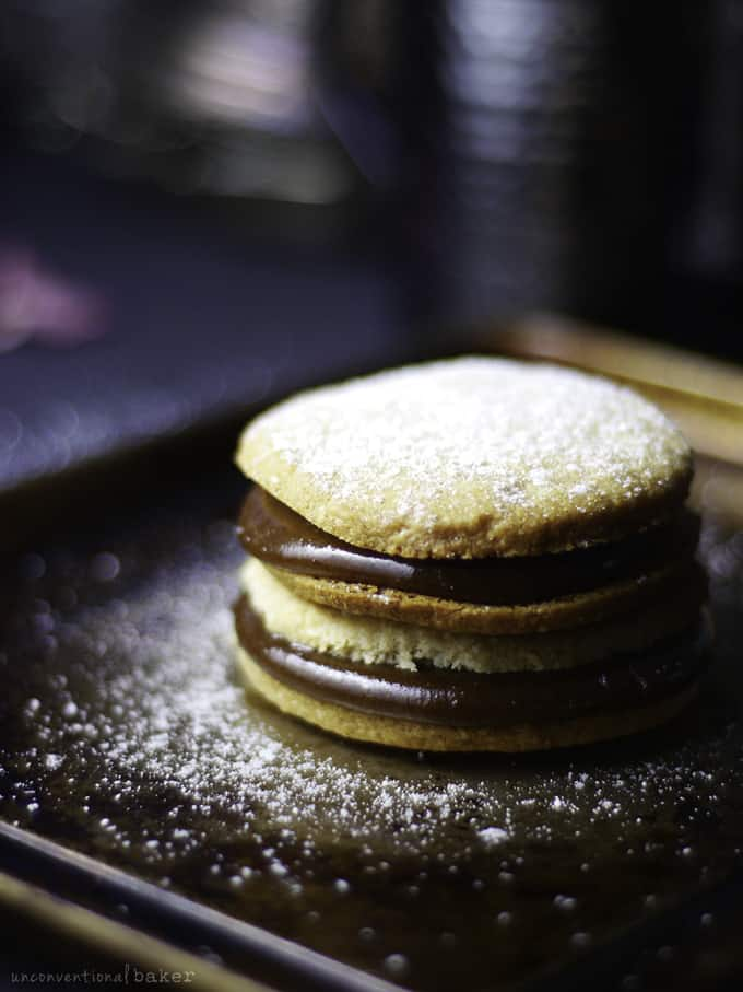 a stack of Alfajores cookies on a black plate with powdered sugar on top