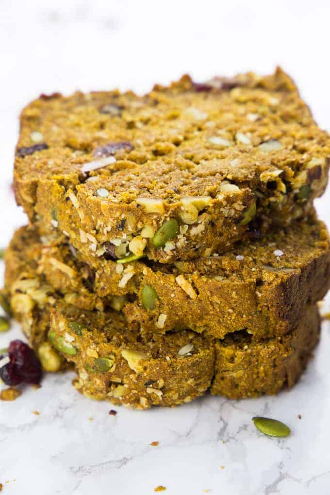 a stack of three slices of vegan pumpkin bread on a marble counter top