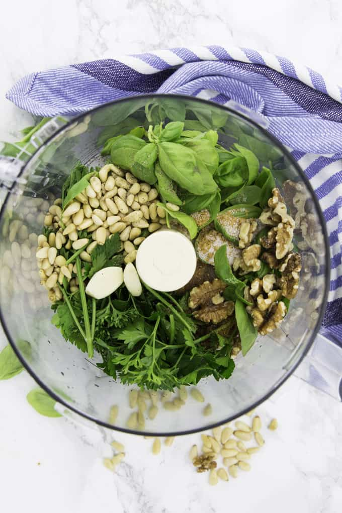 ingredients for vegan pesto in a food processor before blending (walnut, pine nuts, basil, parsley, and garlic)