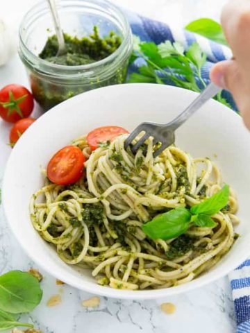 spaghetti with vegan pesto and cherry tomatoes in a white bowl with a hand with a fork rolling up the spaghetti