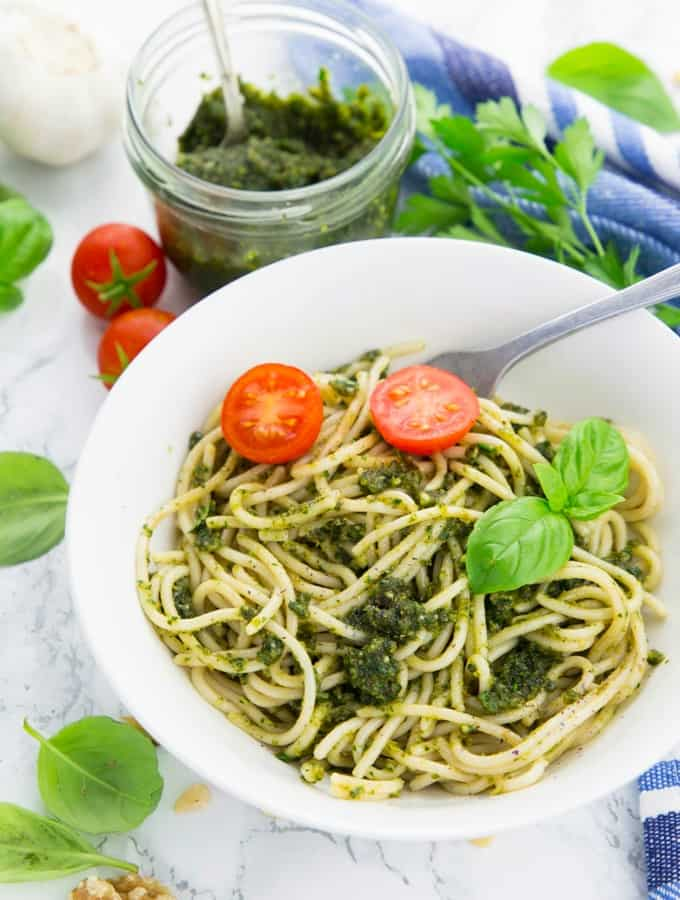 spaghetti with vegan pesto in a white bowl with a fork on a marble counter top with a glass jar of pesto in the background