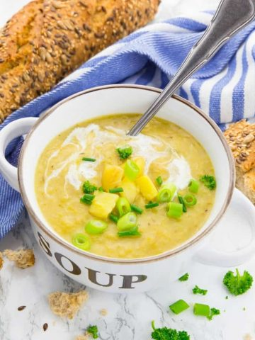 vegan potato soup in a soup bowl with potato cubes, slice green onions, and a swirl of coconut milk on top and bread and a blue dishcloth in the background