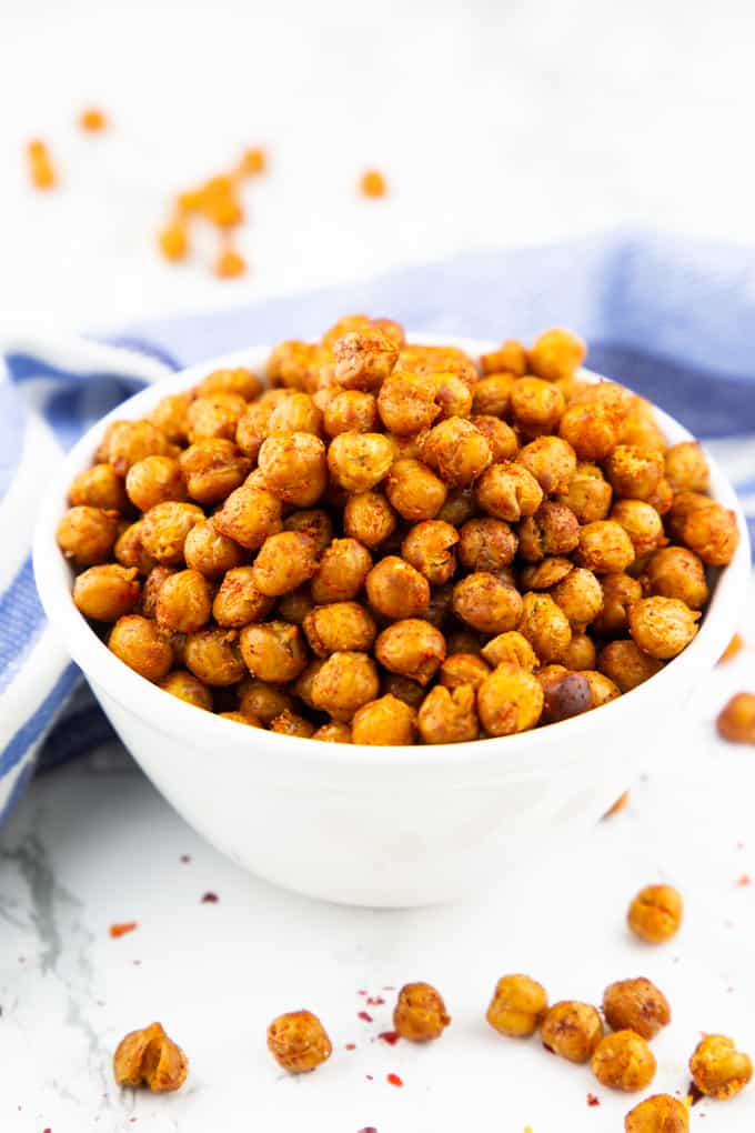 Roasted Chickpeas in a white bowl on a marble counter top with chickpeas on the side