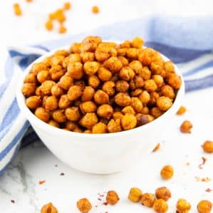 a hand eating roasted chickpeas out of a small white bowl on a marble counter top