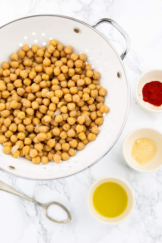 chickpeas in a colander with three little bowls of paprika powder, garlic powder, olive oil and a teaspoon of salt on a marble counter top