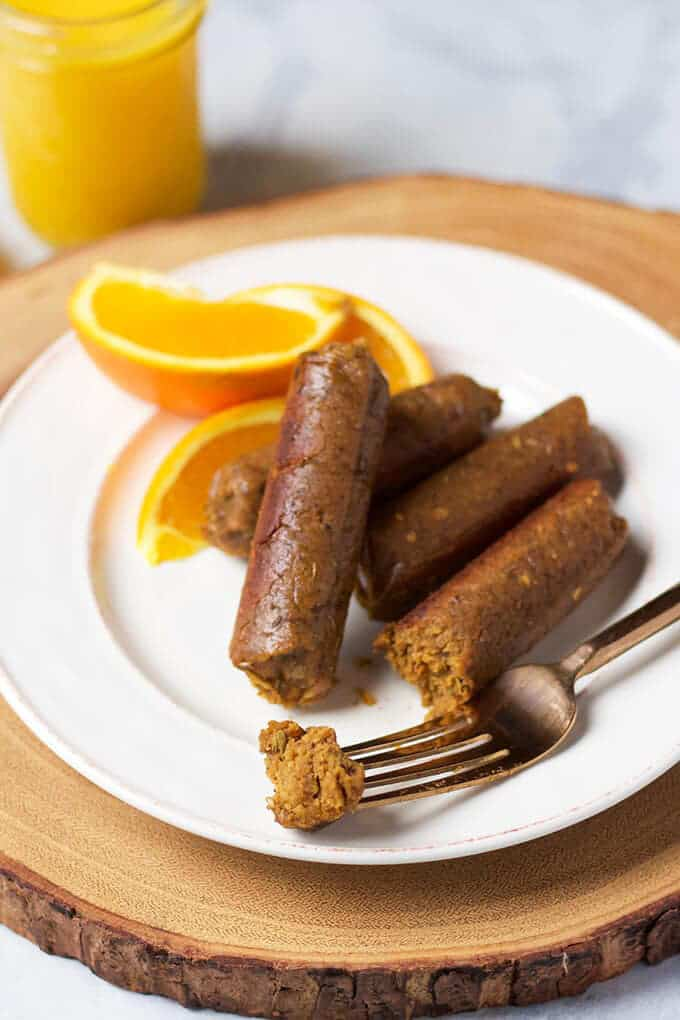 three vegan breakfast sausages on a white plate with a fork and three orange slices on the side and a glass of orange juice in the background