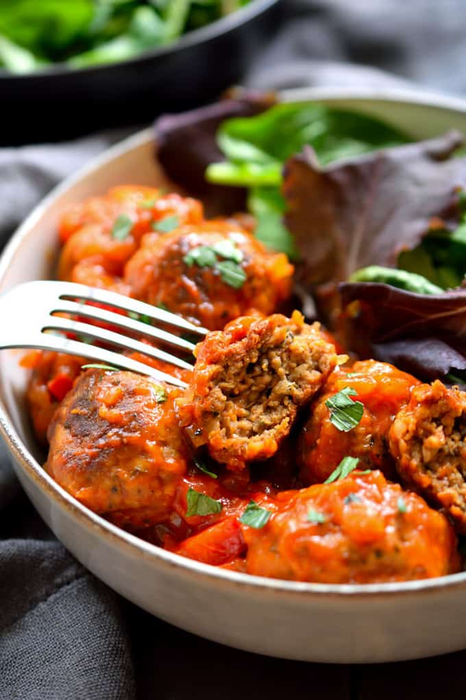 vegan meatballs made with seitan in a bowl with tomato sauce, lettuce, and a fork with a grey dish cloth underneath