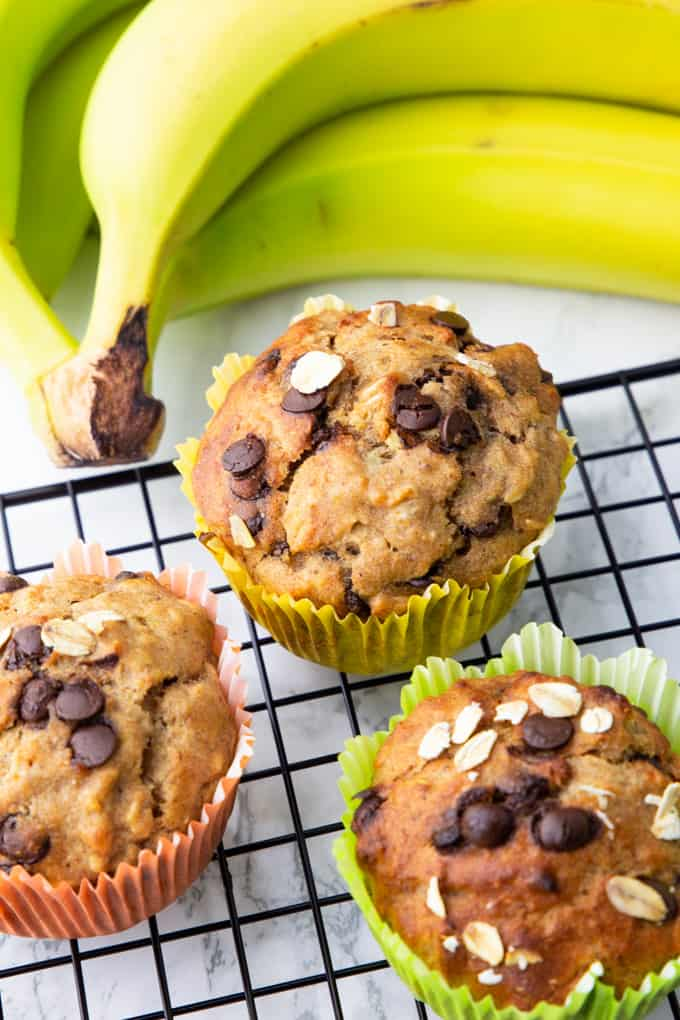 three vegan banana muffins on a cooling rack on a marble counter top with a bunch of bananas in the background