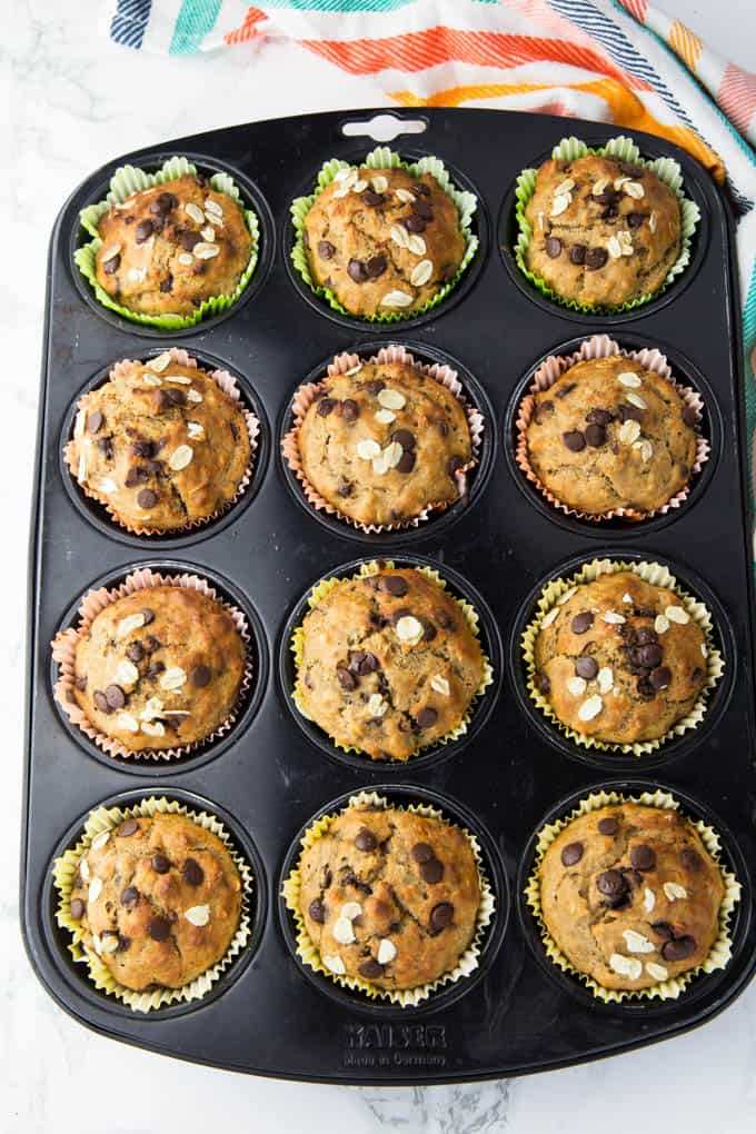 12 vegan banana muffins in a muffin pan after baking on a marble counter top