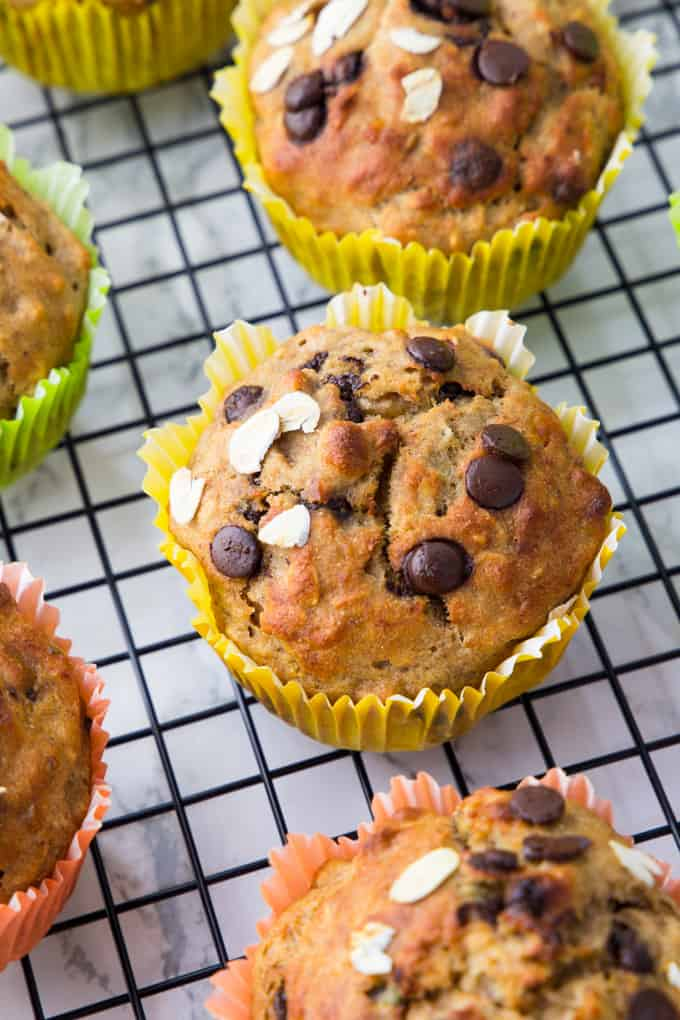 five vegan banana muffins with chocolate chips in colored paper liners on a cooling rack on a marble counter top