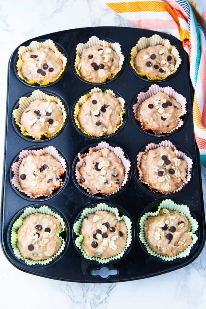 a muffin pan with 12 paper liners filled with muffin batter on a marble counter top before baking