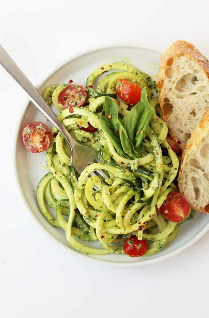 zucchini noodles with pesto and cherry tomatoes on a white plate with two slices of bread on the side on a white counter top