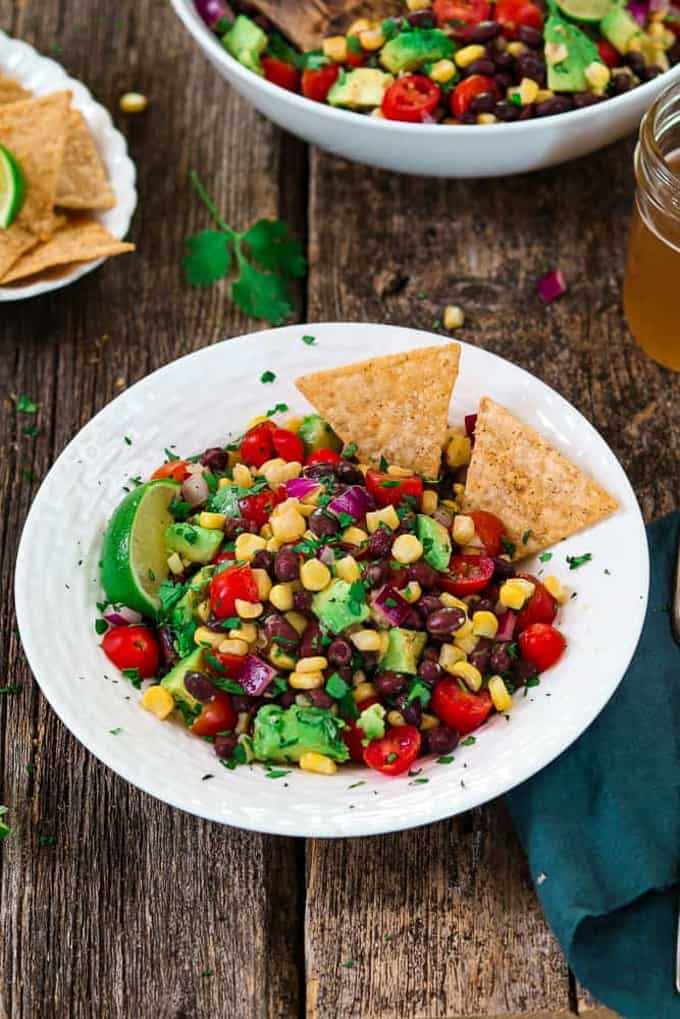 Avocado Black Bean Corn Salad in a white bowl with corn chips on a wooden board with another bowl of corn salad in the background