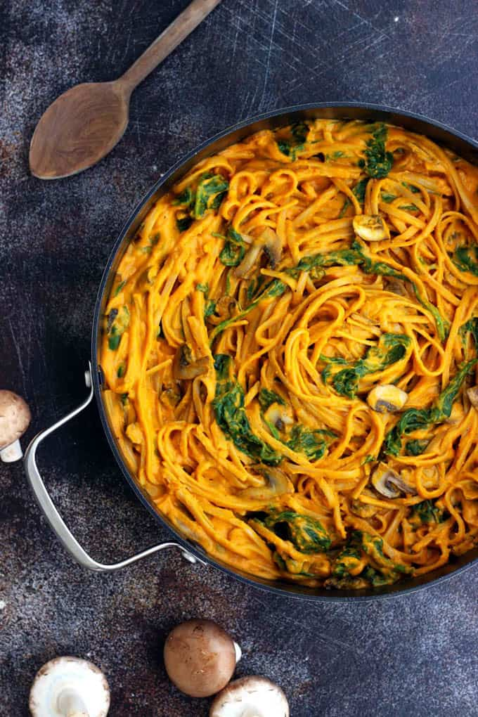 Healthy Pumpkin Pasta with Spinach and Mushrooms by in a pan on a dark counter top with a wooden spoon on the side