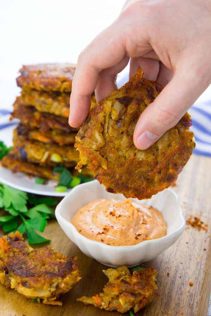 a hand dipping a potato fritter into a small bowl of vegan sriracha mayonnaise with more fritters on a plate in the background