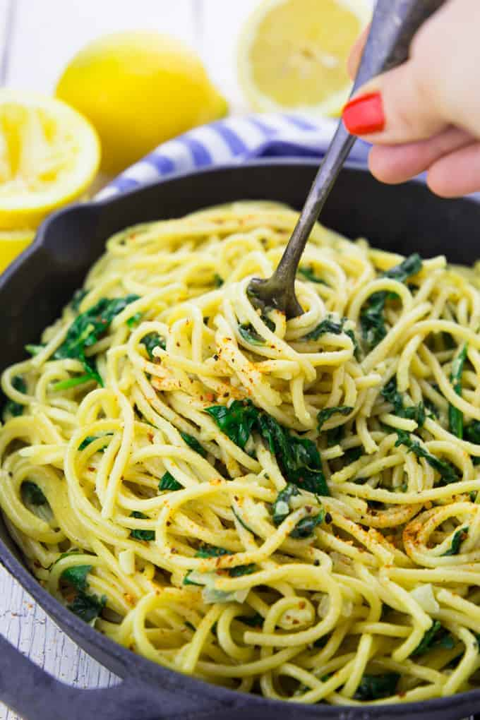 a hand rolling up lemon spaghetti in a cast iron pan with lemons in the background