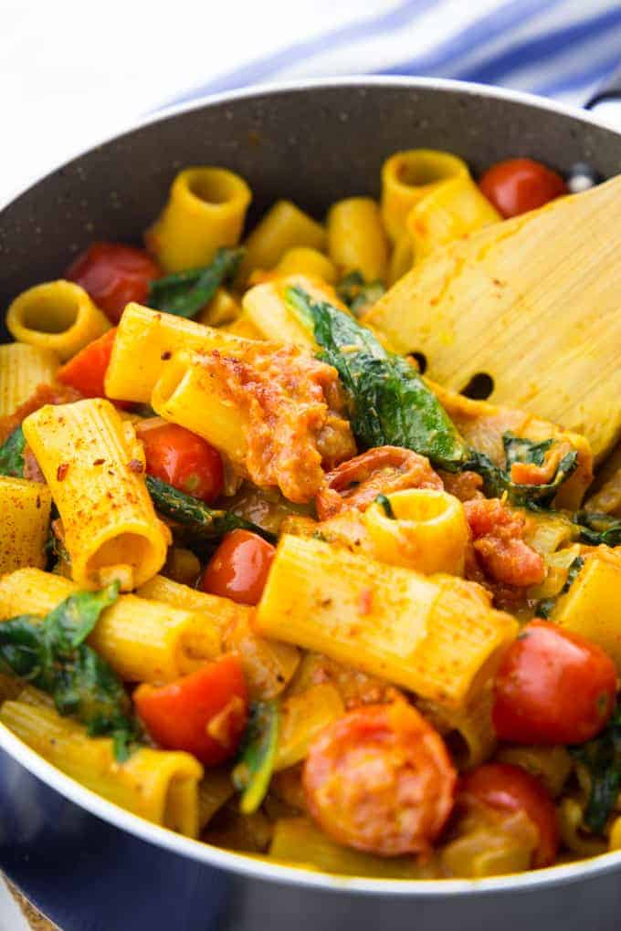 vegan one pot pasta with spinach and tomatoes in a black pot with a wooden spoon