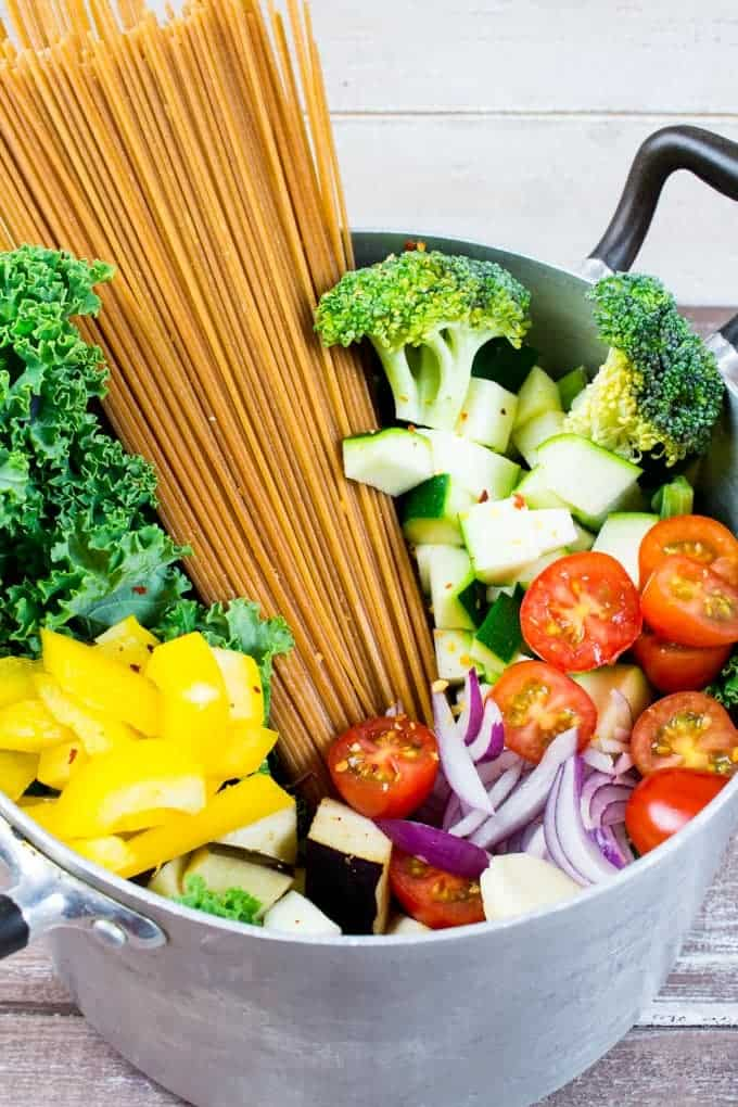 a pot with uncooked spaghetti, kale, yellow bell pepper, broccoli, cherry tomatoes, and red onions