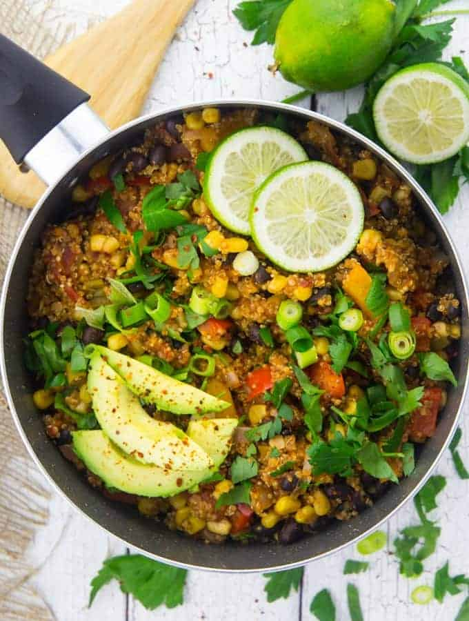 a pot of Mexican quinoa with avocado slices, lime halves, and chopped parsley on top on a white wooden board