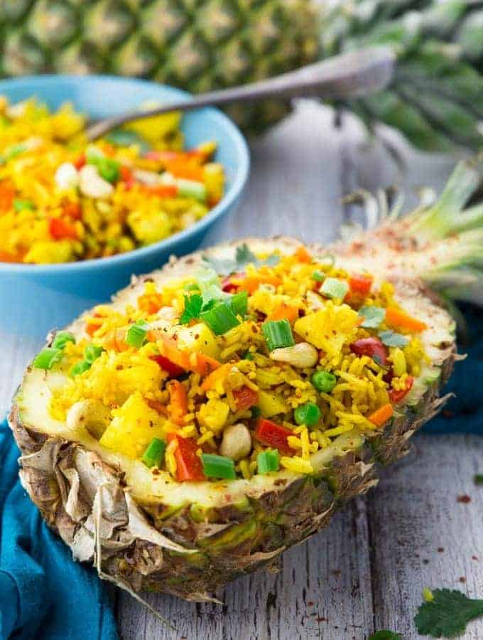 Thai pineapple fried rice in a pineapple half with a bowl of more rice in the background