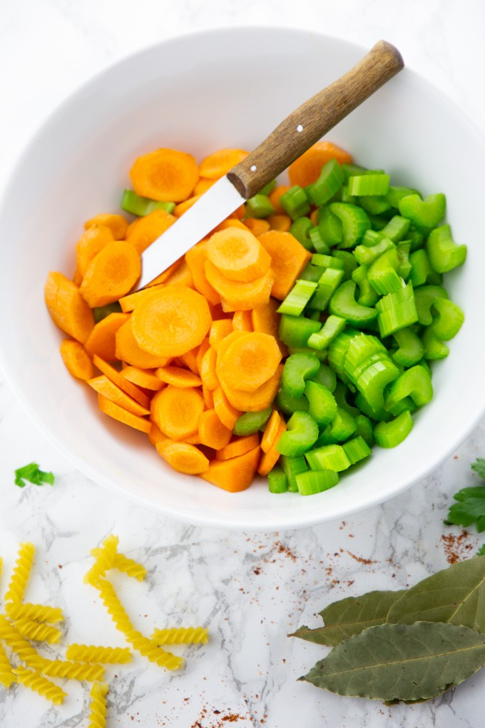 chopped carrots and celery in a white bowl with a knife on a marble counter top